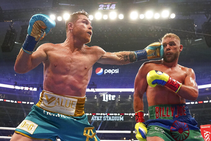 Canelo Alvarez, left, connects against Billy Joe Saunders during a unified super middleweight world championship boxing match, Saturday, May 8, 2021, in Arlington, Texas. (AP Photo/Jeffrey McWhorter)