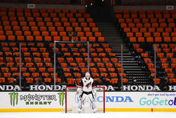 FILE - Arizona Coyotes goaltender Adin Hill guards his net with empty seats behind him during the first period of an NHL hockey game against the Anaheim Ducks in Anaheim, Calif., in this Friday, April 2, 2021, file photo. While the NFL, NBA and Major League Baseball are moving to relax virus protocols when a vast majority of a team's players, coaches and staff are vaccinated, the NHL finds itself in an uncomfortable position. (AP Photo/Jae C. Hong, File)