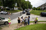 Community members gather near the intersection of Beech and Rively Ave in Alden, Pa., as rescue personal remove two workers who were found dead in a sewer manhole in Alden, on Thursday, July 11, 2019. (Tyger Williams/The Philadelphia Inquirer via AP)
