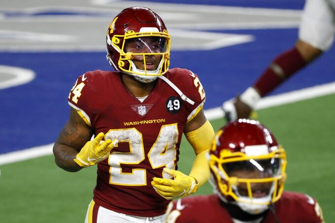Washington Football Team's Antonio Gibson gestures with his right hand as he jogs back to the sideline after scoring a touchdown on a run in the second half of an NFL football game against the Dallas Cowboys in Arlington, Texas, Thursday, Nov. 26, 2020. Gibson scored three touchdowns in the game. (AP Photo/Roger Steinman)