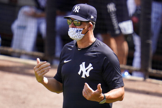 New York Yankees manager Aaron Boone talks with an umpire between innings of a spring training exhibition baseball game against the Philadelphia Phillies in Tampa, Fla., Monday, March 15, 2021. (AP Photo/Gene J. Puskar)