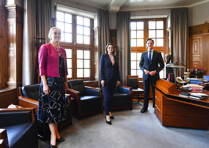 Sviatlana Tsikhanouskaya, former presidential candidate and main figurehead of the Belarus opposition, center, Dutch caretaker Prime Minister Mark Rutte, right, and caretaker Foreign Minister Sigrid Kaag, left, pose for a picture at the start of their meeting in The Hague, Netherlands, Friday, May 28, 2021. (Piroschka van de Wouw/Pool via AP)