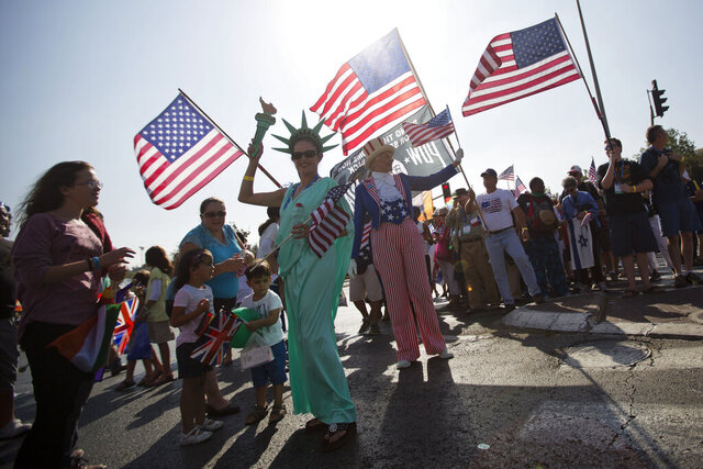 "FILE - In this Oct. 1, 2015 file photo, evangelical Christians from various countries wave American flags in Jerusalem. An evangelical broadcaster who boasted of miraculously securing a TV license in Israel now risks being taken off the air over suspicions of trying to convert Jews to Christianity. The controversy over ""GOD TV"" has put both Israel and its evangelical Christian allies in an awkward position. Evangelical Christians, particularly in the United States, are among Israel's strongest supporters. Israel has long welcomed their political and financial support, especially as their influence has risen during the Trump era. (AP Photo/Sebastian Scheiner, File)"