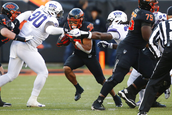 Oklahoma State running back Chuba Hubbard (30) breaks through the TCU line past defensive tackle Ross Blacklock (90) and defensive end Ochaun Mathis (32) for a long touchdown run in the second half of an NCAA college football game in Stillwater, Okla., Saturday, Nov. 2, 2019. (AP Photo/Sue Ogrocki)