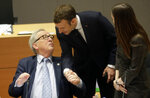 French President Emmanuel Macron, center, greets European Commission President Jean-Claude Juncker during a round table meeting at an EU summit in Brussels, Friday, March 22, 2019. European Union leaders gathered again Friday after deciding that the political crisis in Britain over Brexit poses too great a threat and that action is needed to protect the smooth running of the world's biggest trading bloc. (AP Photo/Olivier Matthys, Pool)