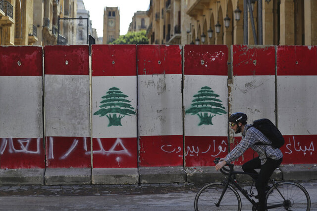 A man rides his bicycle next to a concrete wall installed by authorities to blocks a road leading to the parliament building, in downtown Beirut, Lebanon, Friday, Jan. 24, 2020. Arabic on the wall reads