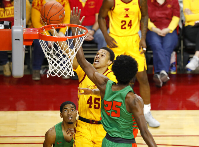 Iowa State guard Rasir Bolton, center, goes up between Florida A&M guard Brendon Myles, left, and forward DJ Jones, right, for a shot during the second half of an NCAA college basketball game Tuesday, Dec. 31, 2019, in Ames, Iowa. Florida A&M won 70-68. (AP Photo/Matthew Putney)