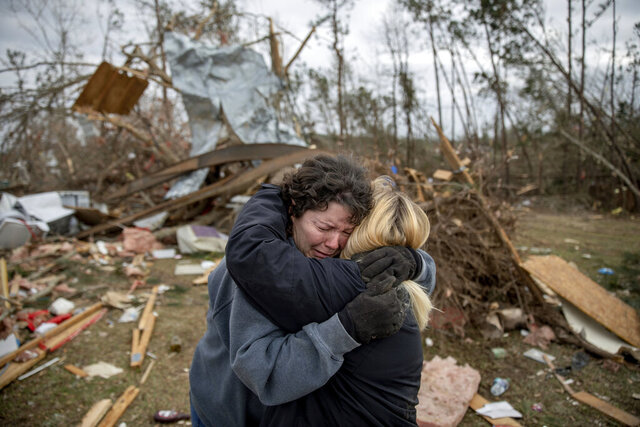 FILE - In this March 4, 2019 file photo, Carol Dean, left, cries while embraced by Lawanda Anderson as Dean sifts through the debris of the home she shared with her husband, David Wayne Dean, who died when a tornado destroyed the house in Beauregard, Ala. This was one of the top stories in Alabama in 2019  .(AP Photo/David Goldman, File)