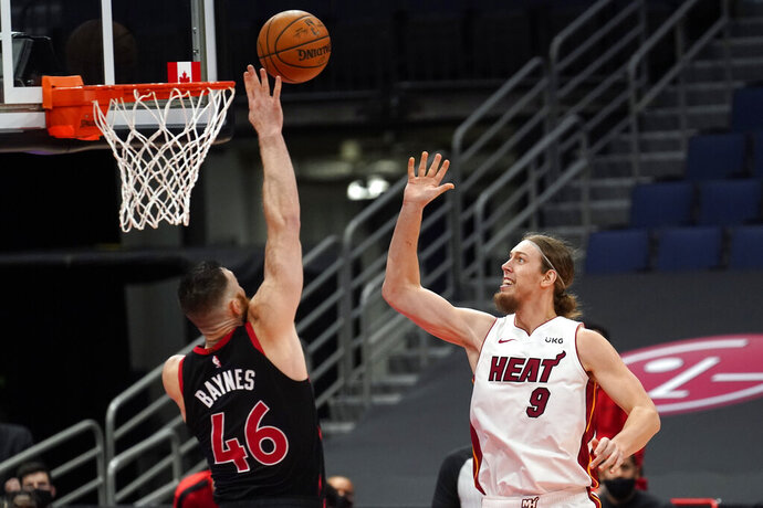 Toronto Raptors center Aron Baynes (46) goes up to block a shot by Miami Heat forward Kelly Olynyk (9) during the second half of an NBA basketball game Friday, Jan. 22, 2021, in Tampa, Fla. (AP Photo/Chris O'Meara)