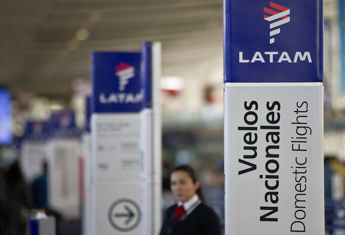 FILE - In this July 25, 2016, file photo, an agent of LATAM airlines stands by the counters at the airport in Santiago, Chile. The South American carrier said Tuesday, May 26, 2020, it is seeking Chapter 11 bankruptcy protection as it grapples with the sharp downturn in air travel sparked by the coronavirus pandemic. (AP Photo/Esteban Felix, File)