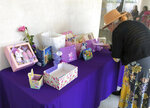 A woman looks a display of mementos at the funeral service for Trinity Love Jones, the 9-year-old whose body was found this month stuffed in a duffel bag along an equestrian trail, at St. John Vianney Catholic Church in Hacienda Heights, Calif., Monday, March 25, 2019. The Hacienda Heights community where her body was found had embraced the child in death during the days she remained unidentified. A park worker found Trinity on March 5. A huge memorial sprang up at the site as community members heard about the case. She was identified the following weekend and prosecutors have since filed murder charges against her mother and the mother's boyfriend. (AP Photo/John Rogers)