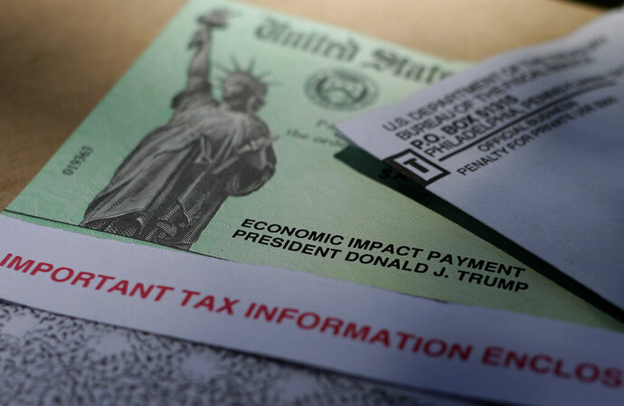 FILE - In this April 23, 2020 file photo, President Donald J.Trump's name is printed on a stimulus check issued by the IRS to help combat the adverse economic effects of the COVID-19 outbreak in San Antonio.  The IRS said that after initial problems, it is getting more of the second round of relief payments to taxpayers. A number of people who filed their taxes with an online preparation service initially found that their economic impact payment did not make it to them directly.   (AP Photo/Eric Gay)