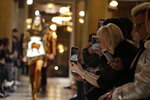 Spectators takes pictures of model wearing creations as part of Versace men's Fall-Winter 2018-19 collection, that was presented in Milan, Italy, Saturday, Jan.13, 2018. (AP Photo/Luca Bruno)