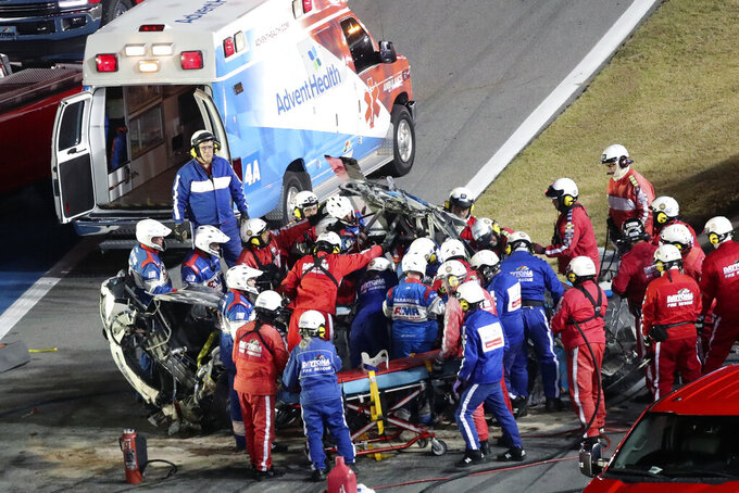 Rescue workers remove Ryan Newman from his car after he was involved in a wreck on the last lap of the NASCAR Daytona 500 auto race at Daytona International Speedway, Monday, Feb. 17, 2020, in Daytona Beach, Fla. (AP Photo/David Graham)
