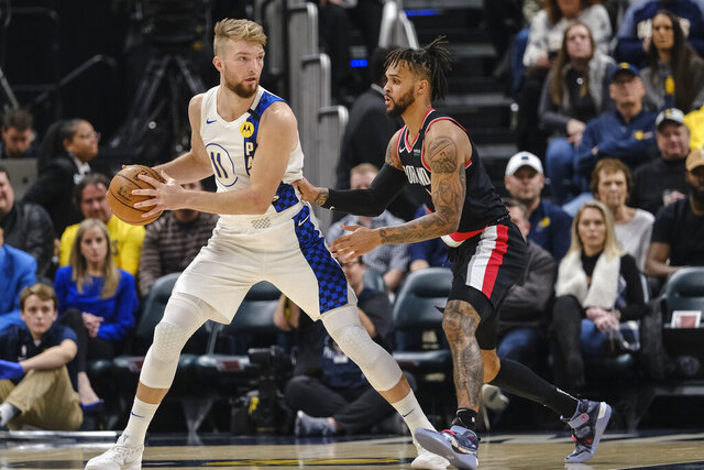 Indiana Pacers forward Domantas Sabonis, left, looks to pass around Portland Trail Blazers center Moses Brown during the first half of an NBA basketball game in Indianapolis, Thursday, Feb. 27, 2020. (AP Photo/AJ Mast)