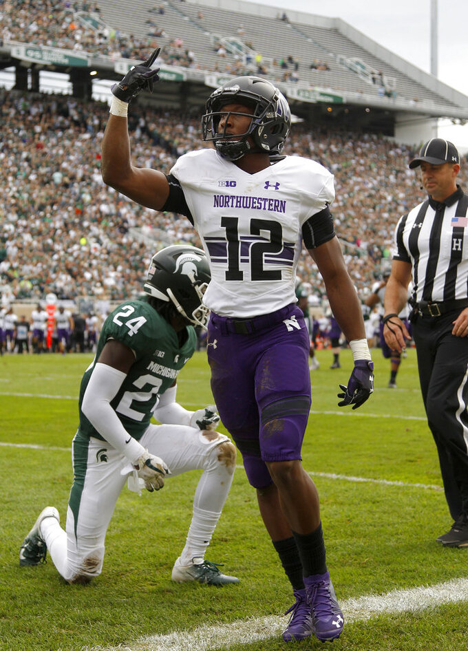Northwestern's JJ Jefferson (12) celebrates his touchdown reception against Michigan State's Tre Person (24) during the second quarter of an NCAA college football game, Saturday, Oct. 6, 2018, in East Lansing, Mich. (AP Photo/Al Goldis)