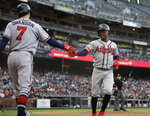 Atlanta Braves' Ozzie Albies, right, is congratulated by Dansby Swanson (7) after scoring on a wild pitch by San Francisco Giants' Jeff Samardzija during the second inning of a baseball game Wednesday, May 22, 2019, in San Francisco. (AP Photo/Ben Margot)