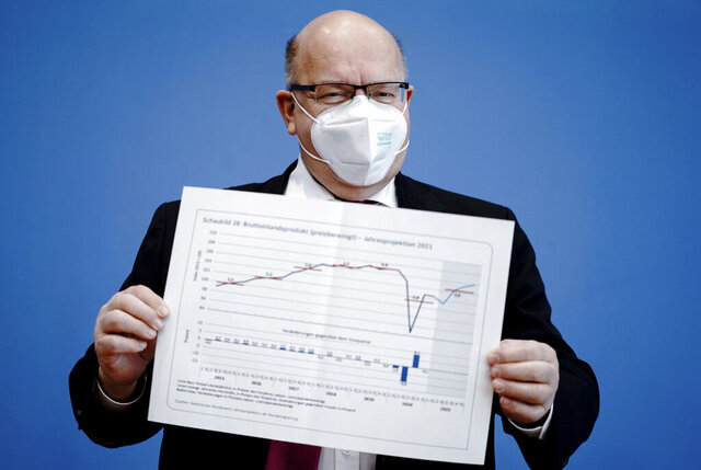 German Economy Minister Peter Altmaier presents the annual Economic Report 2021 at the federal press Ccnference in Berlin, Germany, Wednesday, Jan 27, 2021. The German government has revised its growth forecast for this year down to 3% as Europe's biggest economy faces persistent headwinds from the coronavirus pandemic. (Kay Nietfeld/dpa via AP)