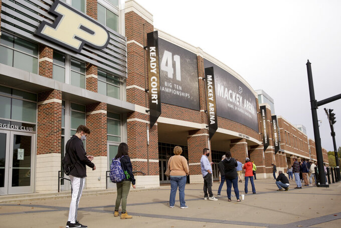 FILE - In this Oct. 14, 2020, file photo, voters line up outside Purdue University's Mackey Arena for early voting ahead of the 2020 general election, in West Lafayette, Ind. The NCAA announced Monday, Jan. 4, 2020, that this year's 67 men's basketball tournament games including the Final Four will be played entirely in Indiana. Games will be played on two courts inside Lucas Oil Stadium as well as at Bankers Life Fieldhouse, Hinkle Fieldhouse, Indiana Farmers Coliseum, Mackey Arena at Purdue and Assembly Hall in Bloomington. (Nikos Frazier/Journal & Courier via AP, File)/