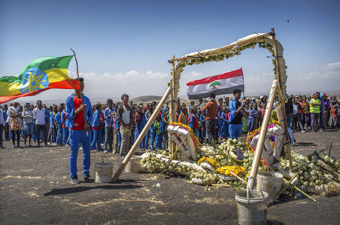 Students from Hama elementary school, who walked an hour and a half from their school in the surrounding area to pay their respects, stand next to floral tributes at the scene where the Ethiopian Airlines Boeing 737 Max 8 crashed shortly after takeoff on Sunday killing all 157 on board, near Bishoftu, south-east of Addis Ababa, in Ethiopia Friday, March 15, 2019. Analysis of the flight recorders has begun in France, the airline said Friday, while in Ethiopia officials started taking DNA samples from victims' family members to assist in identifying remains. (AP Photo/Mulugeta Ayene)