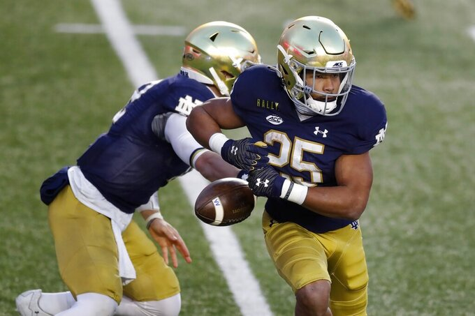 Notre Dame running back Chris Tyree (25) fumbles the ball on a handoff from quarterback Ian Book during the first half of an NCAA college football game against Boston College, Saturday, Nov. 14, 2020, in Boston. (AP Photo/Michael Dwyer)
