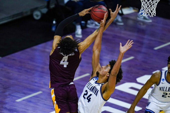 Villanova forward Jeremiah Robinson-Earl (24) blocks the shot of Winthrop forward Kelton Talford (4) in the first half of a first round game in the NCAA men's college basketball tournament at Farmers Coliseum in Indianapolis, Friday, March 19, 2021. (AP Photo/Michael Conroy)