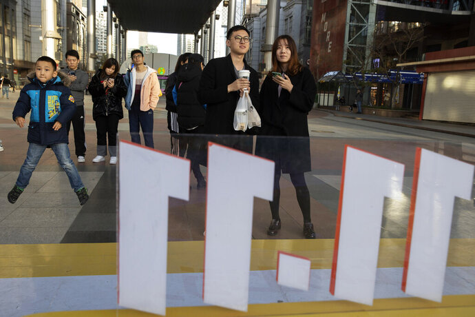 In this photo taken Sunday, Nov. 10, 2019, shoppers react as they take part in a promotion ahead of Nov. 11 Singles day in Beijing. Chinese online shoppers hunt bargains on Singles Day, a holiday invented in the 1990s that has become the world's busiest day for online commerce. (AP Photo/Ng Han Guan)