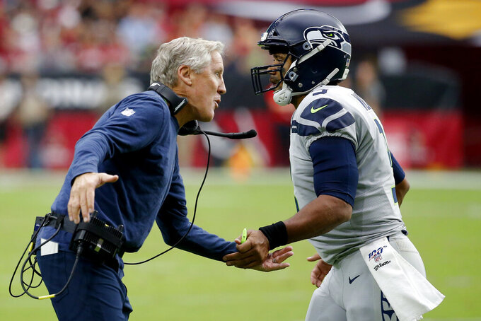 Seattle Seahawks head coach Pete Carroll greets Russell Wilson after a touchdown pass during the first half of an NFL football game against the Arizona Cardinals, Sunday, Sept. 29, 2019, in Glendale, Ariz. (AP Photo/Rick Scuteri)