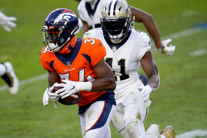 Denver Broncos defensive back Essang Bassey (34) runs after an interception as New Orleans Saints running back Alvin Kamara (41) pursues during the second half of an NFL football game, Sunday, Nov. 29, 2020, in Denver. (AP Photo/David Zalubowski)