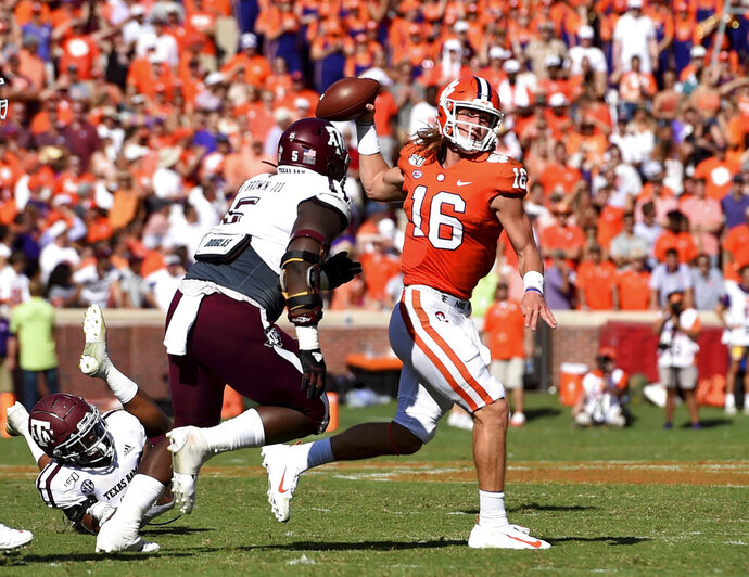 Clemson quarterback Trevor Lawrence (16) passes while pressured by Texas A&M's Bobby Brown during the first half of an NCAA college football game Saturday, Sept. 7, 2019, in Clemson, S.C. (AP Photo/Richard Shiro)