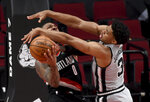 Portland Trail Blazers guard Damian Lillard, left, is fouled by San Antonio Spurs forward Keldon Johnson, right, as he drives to the basket during the second half of an NBA basketball game in Portland, Ore., Monday, Jan. 18, 2021. (AP Photo/Steve Dykes)