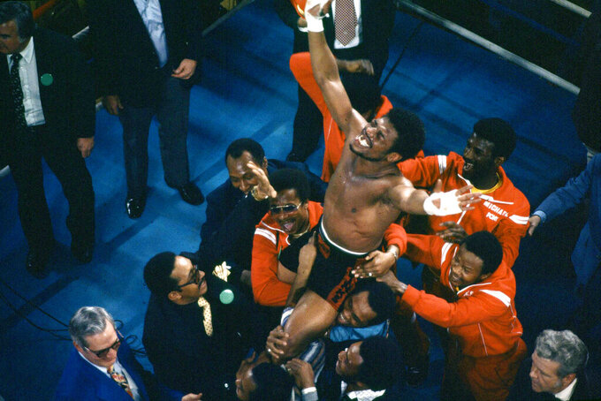 FILE - In this Feb. 15, 1978, file photo, Leon Spinks celebrates as his entourage holds him aloft after his 15-round split decision victory over world heavyweight boxing champion Muhammad Ali in Las Vegas. Former heavyweight champion Leon Spinks Jr. died Friday night, Feb. 5, 2021, after battling prostate and other cancers. He was 67. (AP Photo/FIle)