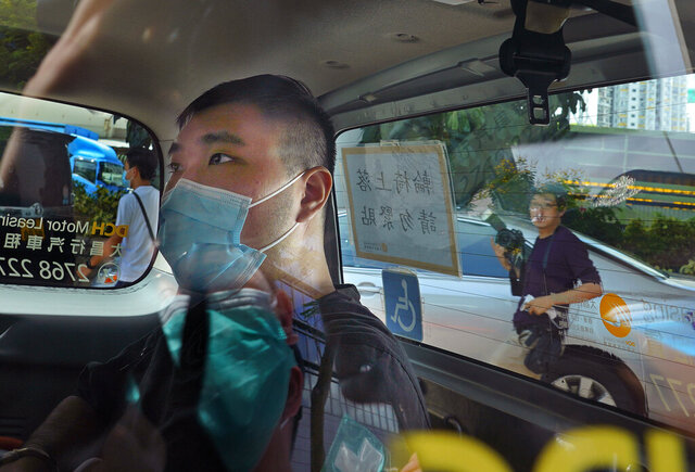 A 23-year-old man, Tong Ying-kit, arrives at a court in a police van in Hong Kong Monday, July 6, 2020. Tong has become the first person in Hong Kong to be charged under the new national security law, for allegedly driving a motorcycle into a group of policemen while bearing a flag with the