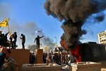 Protesters set fires in front of the U.S. embassy compound, in Baghdad, Iraq, Tuesday, Dec. 31, 2019. Dozens of angry Iraqi Shiite militia supporters broke into the U.S. Embassy compound in Baghdad on Tuesday. The breach at the embassy followed U.S. airstrikes on Sunday that killed 25 fighters of the Iran-backed militia in Iraq, the Kataeb Hezbollah. (AP Photo/Khalid Mohammed)