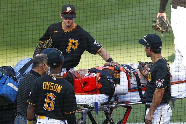 Pittsburgh Pirates Kevin Newman, top, Adam Frazier, right, and Jarrod Dyson (6) check on Phillip Evans (64) as he is taken from the filed on a stretcher after he collided with Gregory Polanco along the right field fence while chasing a fly ball by Detroit Tigers' Miguel Cabrera in the sixth inning of a baseball game Saturday, Aug. 8, 2020, in Pittsburgh. Polanco stayed in the game. (AP Photo/Keith Srakocic)