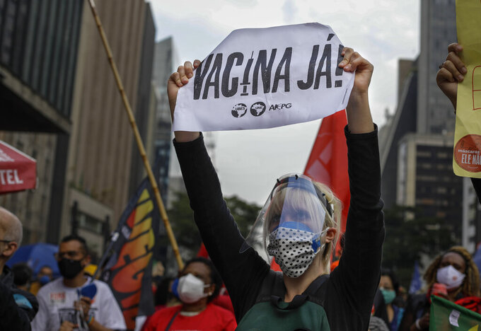 """A demonstrator holds a sign that reads in Portuguese; """"'Vaccine now"""", during a protest against Brazilian President Jair Bolsonaro and his handling of the COVID-19 pandemic on Paulista Avenue, in Sao Paulo, Brazil, Saturday, June 19, 2021. Brazil's COVID-19 death toll is expected to surpass the milestone of 500,000 deaths on Saturday night. (AP Photo/Marcelo Chello)"""