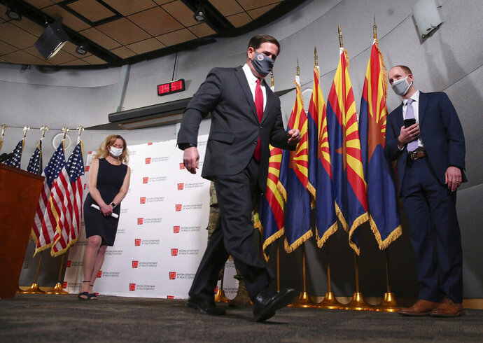 "Ariz. Gov. Doug Ducey walks out after addressing the media on COVID-19 during a news conference in Phoenix on Wednesday, Nov. 18, 2020. Behind him is Dr. Cara Christ.  Health officials are begging people not to travel for Thanksgiving and asking families to resist inviting anyone over to the house who does not already live there.  ""Don't let down your guard, even around close friends and relatives who aren't members of your household,"" Arizona's health department said on Twitter.(Michael Chow/The Arizona Republic via AP)"