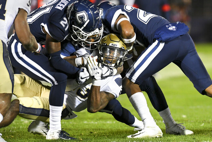 Navy wide receiver Myles Fells (23) is taken down by Connecticut defenders during the second half of an NCAA college football game Friday, Nov. 1, 2019, in East Hartford, Conn. (AP Photo/Stephen Dunn)