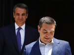 Greece's newly-elected prime minister Kyriakos Mitsotakis, background, looks on as outgoing prime minister Alexis Tsipras, leaves the Maximos Mansion in Athens, Monday, July 8, 2019. Mitsotakis' New Democracy party won 39.8% of the vote, giving him 158 seats in the 300-member parliament, a comfortable governing majority. (AP Photo/Thanassis Stavrakis)