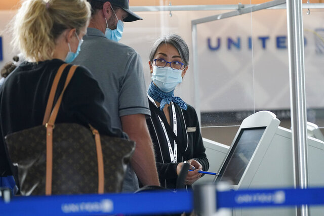 Travellers check in at a United Airlines kiosk with help from a United employee in the main terminal of Denver International Airport Thursday, Oct. 1, 2020, in Denver. (AP Photo/David Zalubowski)