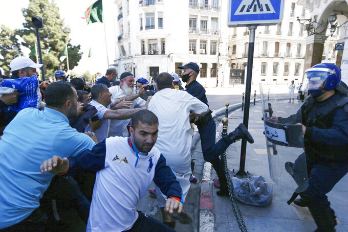 FILE - In this May 7, 2021 file photo, demonstrators supporting the Hirak pro-democracy movement are pushed by police officers in Algiers, Friday, May 7, 2021. A crackdown on the pro-democracy Hirak movement, with hundreds arrested around Algeria during last week's 117th Friday march, casts a pall over presidential efforts to give a new face to a nation whose army plays a backseat role in governance. (AP Photo/Anis Belghoul, File)