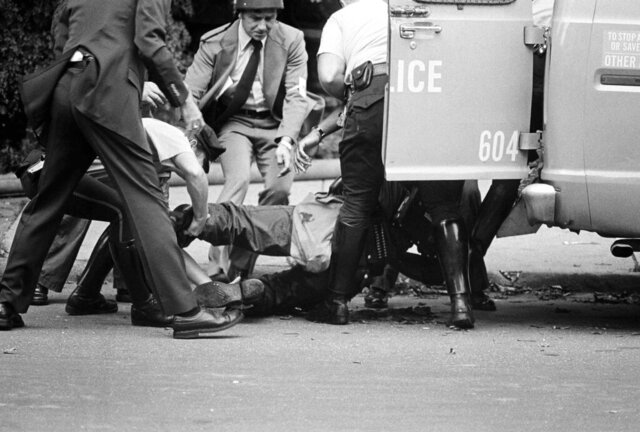 FILE—In this file photo from August 8, 1978, gunshot victim James Ramp is lifted into police van after he was shot during confrontation with the group MOVE in Philadelphia's west side. Ramp was killed and at least 10 other persons were injured in a shootout. An attorney for Chuck Sims Africa, who was one of the MOVE group members convicted of third-degree murder in the 1978 shooting death of Officer Ramp, posted on Twitter that the man had been released from a Pennsylvania prison. Africa was the last of the so-called MOVE 9 to be paroled. Attorney Brad Thomson confirmed via email that Africa had been released Friday, Feb. 7, 2020. (AP Photo/Paul Shane, File)