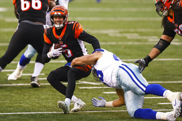 Cincinnati Bengals quarterback Ryan Finley (5) is sacked by Dallas Cowboys defensive tackle Tyrone Crawford (98) in the second half of an NFL football game in Cincinnati, Sunday, Dec. 13, 2020. (AP Photo/Aaron Doster)
