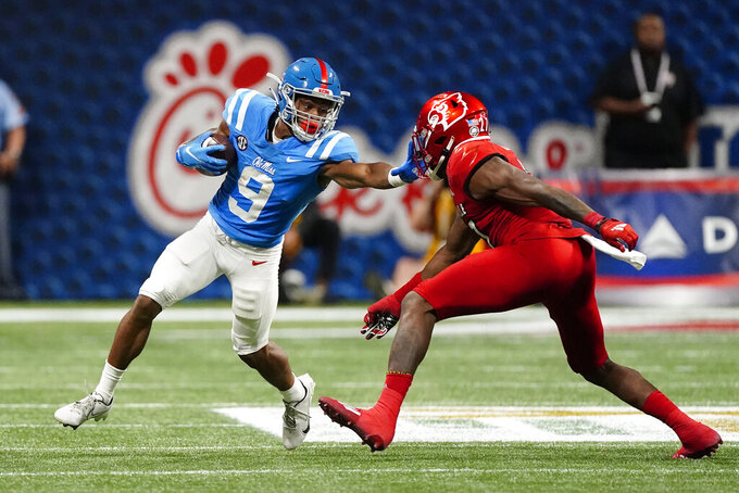 Mississippi running back Jerrion Ealy (9) fends off Louisville defensive back Kenderick Duncan (27) after a catch during an NCAA college football game, Monday, Sept. 6, 2021, in Atlanta. (AP Photo/John Bazemore)
