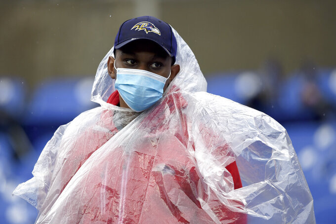 An usher wears a face mask to protect against COVID-19 and a poncho for the rain prior to an NFL football game between the Baltimore Ravens and the Pittsburgh Steelers, Sunday, Nov. 1, 2020, in Baltimore. (AP Photo/Gail Burton)
