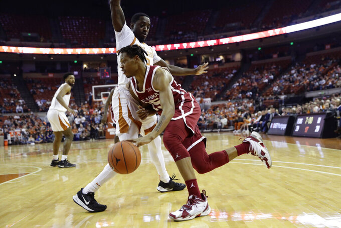 Oklahoma guard Alondes Williams (15) drives around Texas guard Courtney Ramey (3) during the first half of an NCAA college basketball game in Austin, Texas, Wednesday, Jan. 8, 2020. (AP Photo/Eric Gay)