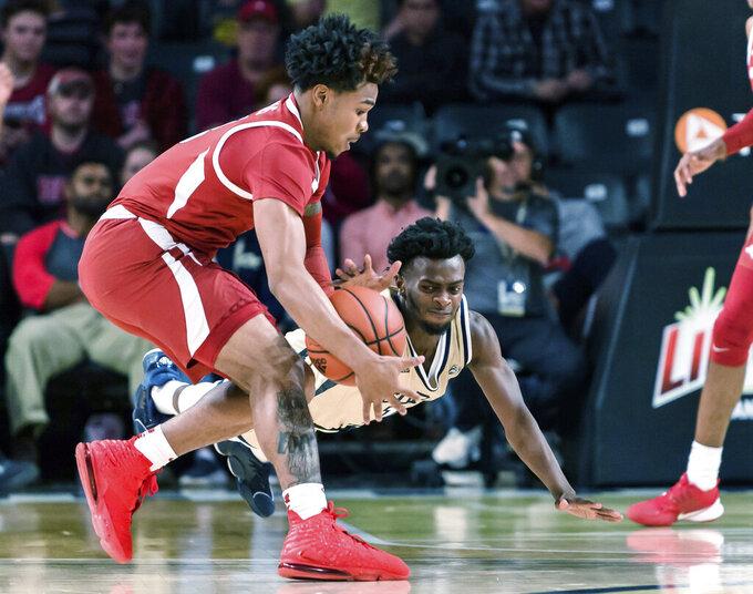 Georgia Tech guard Bubba Parham (11) dives for a loose ball grabbed by Arkansas guard Desi Sills (3) in the first half of an NCAA college basketball game Monday, Nov. 25, 2019, in Atlanta. (AP Photo/Danny Karnik)