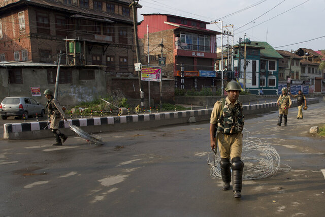 FILE - In this Wednesday, Aug. 7, 2019, file photo, Indian paramilitary soldiers drag barbwire as they prepare to impose curfew in Srinagar, Indian controlled Kashmir. Envoys from more than 20 countries arrived in Indian-controlled Kashmir on Wednesday, Feb. 12, 2020, the second visit by a delegation of New Delhi-based foreign diplomats since the Prime Minister Narendra Modi's Hindu nationalist-led government stripped the region of its semi-autonomous status in August last year. The move was accompanied by a harsh crackdown, with New Delhi sending tens of thousands of additional troops to the already heavily militarized region, imposing a sweeping curfew, arresting thousands and cutting virtually all communications. (AP Photo/Dar Yasin)