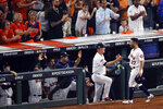 """FILE- In this Saturday, Oct. 19, 2019, file photo, Houston Astros second baseman Jose Altuve is greeted at the dugout manager AJ Hinch after scoring on a fielder's choice in the sixth inning in Game 6 of baseball's American League Championship Series against the New York Yankees in Houston. The AL champions have been dogged by allegations of spying, most recently during this year's ALCS against the Yankees. Houston players were suspected of whistling in the dugout to communicate pitch selection to batters, an allegation manager AJ Hinch called """"ridiculous."""" (AP Photo/Sue Ogrocki, File)"""