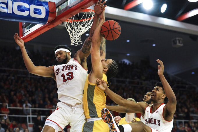St. John's forward Marvin Clark II blocks a shot from Marquette forward Theo John during the first half of an NCAA college basketball game Tuesday, Jan. 1, 2019, in New York. (AP Photo/Kevin Hagen).